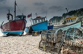 stock photo of lobster boat  - Fishing boats moored on a pebble beach with lobster pots - JPG