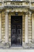 Large wooden entrance door with stone pillars to the sides
