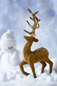 Reindeer Christmas figure in snow scene with snowman in background