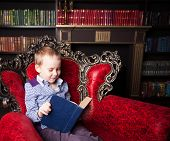 Boy reading book at home. Child indoors
