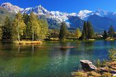 Lake with cold water surrounded by trees and snow-capped mountains. City park in the Alpine resort
