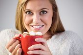 Pretty blonde enjoying hot chocolate on the couch at home in the living room