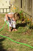 Little gardener: Cute girl watering flowers in the garden
