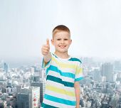 happiness, childhood and people concept - smiling little boy in casual clothes showing thumbs up ove