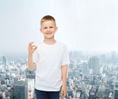 advertising, people and childhood concept - smiling little boy in white blank t-shirt over city back