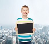 education, school, advertisement and people concept - smiling little boy holding blank black chalkbo
