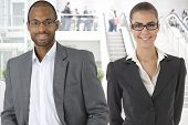 Closeup portrait of young businessman and businesswoman at office building, at lobby.