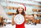 christmas, winter, holidays, time and people concept - smiling woman in santa helper hat and red dre