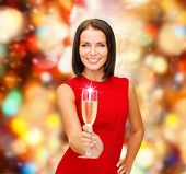 party, drinks, holidays, christmas and celebration concept - smiling woman in red dress with glass o