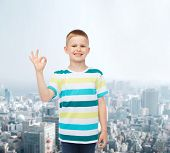 childhood, gesture and people concept - smiling little boy in casual clothes making ok gesture over