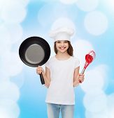 advertising, childhood, cooking and people - smiling girl in white t-shirt and cooking hat holding p