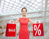 shopping, sale, gifts, christmas and holiday concept - smiling young woman in red dress with shoppin