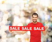sale, shopping, christmas, holidays and people concept - smiling man in red t-shirt with sale sign