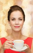 leisure, happiness and drink concept - smiling woman in red dress with cup of coffee over golden lig