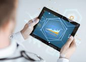 medicine, technology and people concept - close up of doctor holding tablet pc with graph on screen