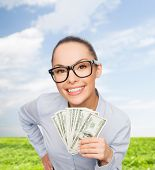business, money, nature and banking concept - smiling businesswoman in eyeglasses with dollar cash m