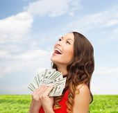 sale, nature, banking and people concept - smiling woman in red dress with us dollar money