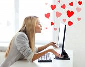 virtual relationships, online dating and social networking concept - woman sending kisses with compu