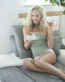 Beautiful young woman looking at tempting cake while sitting on sofa in house