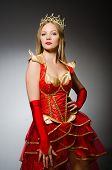 Queen in red costume against dark background