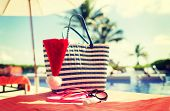summer holidays, christmas and vacation concept - santa helper hat, bag, sunscreen and sunglasses