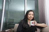 Portrait of happy young woman holding coffee mug in living room