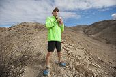 stock photo of landforms  - Determined senior man holding water bottle while standing on mountain - JPG
