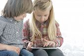 Brother and sister using tablet PC in bedroom