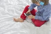 High angle view of boy listening to music through smart phone in bedroom