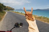 Guy Driving Motorbike Along Amazing Tropical Road And Seaside And Showing Rock Sign