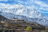 Tibetian House Hight In Himalays With Snowy Mountain Peak On Background