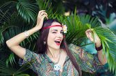 Hippie-girl With Tropical Flower In Her Long Hair Smiling And Poking