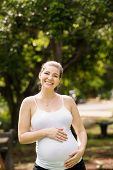 Portrait Of Happy And Smiling Pregnant Woman In Park