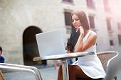 Business woman portrait outdoors working with laptop