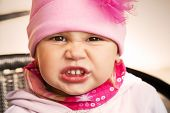 Closeup Portrait Of Funny Angry Baby Girl In Pink