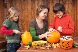 stock photo of jack o lanterns  - Woman helping kids to carve their pumpkin Halloween jack - JPG