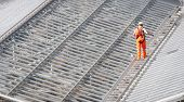 Male Worker Walking On A Roof Metal Structure