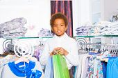 African boy between rows with clothes at store