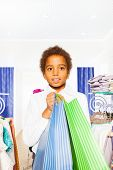 African boy wears white shirt with bags in store