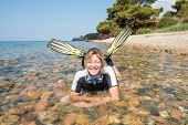 picture of fin  - Young lady smiling and relaxing in the sea on a beach wearing a wetsuit - JPG