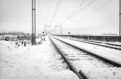 Railroad in the country, winter landscape with snow. Black and white photo