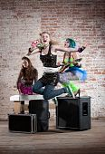 stock photo of groupies  - Young all girl punk rock band performs in a warehouse - JPG