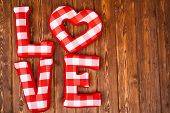 Love word of plush red letters on wood background. Full plaid textile