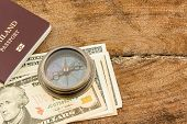 Compass, passport with dollar banknote on wood background.