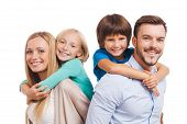picture of family bonding  - Happy family of four bonding to each other and smiling while standing against white background - JPG