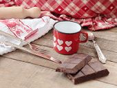 Modica Chocolate Bar Inside Hearts Decorated Mug With Kitchen Utensils Background