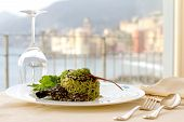 Serving Dish With Home Made Pasta With Rocket Pesto And Pine Nuts Crusted Squid Ink Against Camogli
