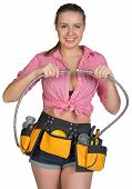 Woman in tool belt holding flexible tap hose