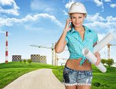 Woman in hard hat, holding drawing rolls calling on the phone