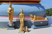 Three small Buddha statues at the base of a stupa, Samui, Thailand.